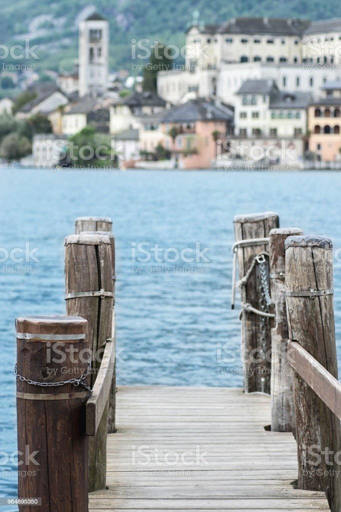 View of the city San Giulio old pier  and the island of San Giulio, Lake Orta,Piedmont , Italy royalty-free stock photo