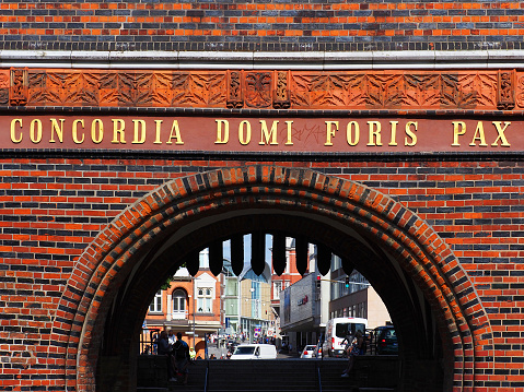 View of the city streets through the Holstein Gate or Holstentor. The inscription above the gate in Latin: harmony within, peace without (concordia domi foris pax)