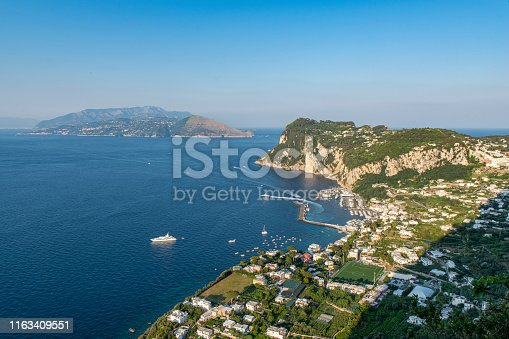 View of the coastline and Capri town in the Island of Capri in the Tyrrhenian Sea in Italy. Boats are floating next to the coast.