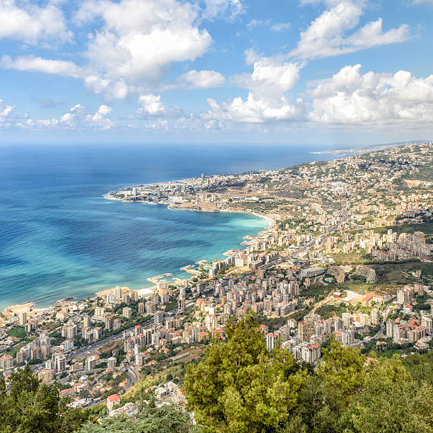 View of the coastline from Harissa, Lebanon View of the coastline north of Beirut from the top of the mountain of Harissa in Lebanon. The turquoise water of the mediterranean is surrounded by buildings and green under a dramatic partially clouded sky beirut stock pictures, royalty-free photos & images