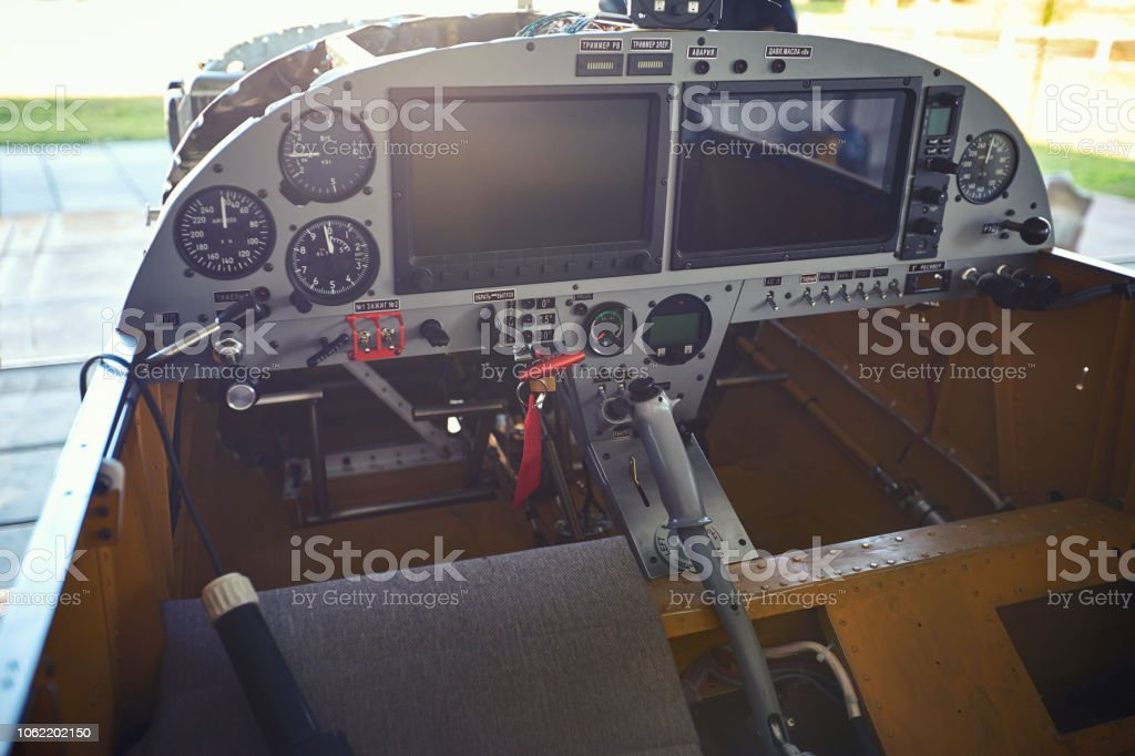 View of the cockpit and control levers of a single-engine aircraft parked. stock photo