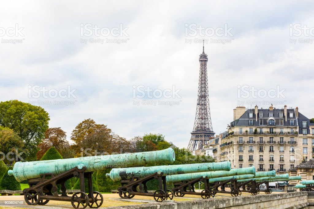 View of the Eiffel tower with the row of bronze cannon of the 'Place des Invalides' in the foreground and a typical parisian building in the background stock photo
