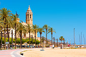SITGES, CATALUNYA, SPAIN - JUNE 20, 2017: View of the embankment and hurch of Sant Bartomeu and Santa Tecla. Copy space for text.