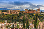 Spanish city of Granada in Andalusia with clouds and mountains in the background. Historic Alhambra fortress with trees and buildings on a hill. Red tile roofs of the buildings to the autumn mood