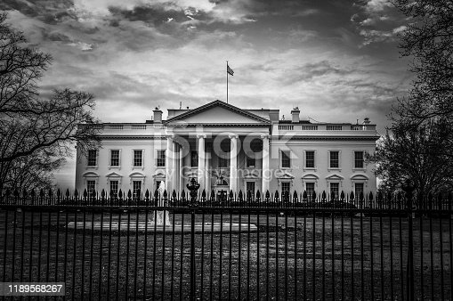 Black and white image of the United States presidential residence with flag on roof in the nations capital
