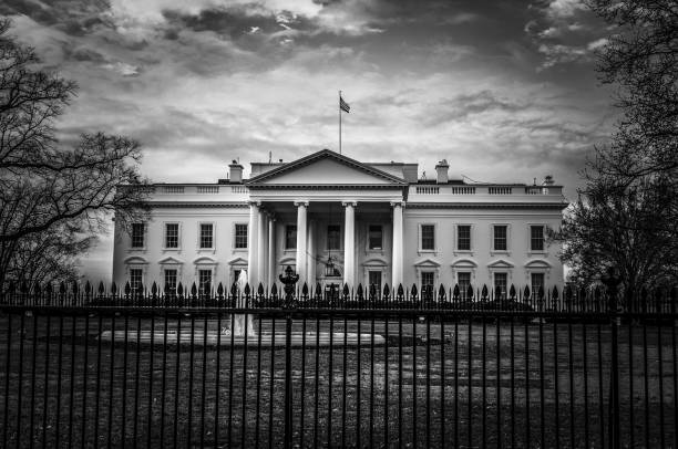 view of the front entrance to the white house in washington dc with iron fence in the foreground - white house стоковые фото и изображения