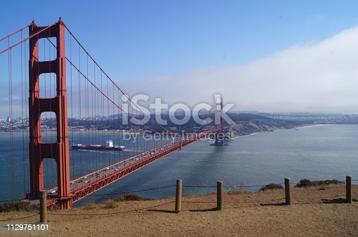 A view of the Golden Gate Bridge and San Francisco Bay Area with a ship in the middle ground and Clouds obscuring a portion.