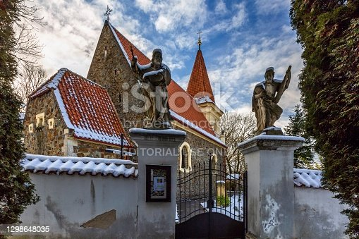 Prague, Czech Republic - January 13 2021: A gate and two saint statues at Petrovice. Winter day with blue sky and white clouds.