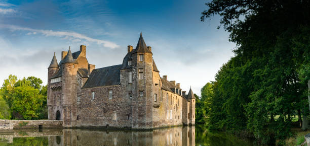 Blick auf das historische Schloss Trecesson im Broceliande-Wald mit Reflexionen im Teich – Foto