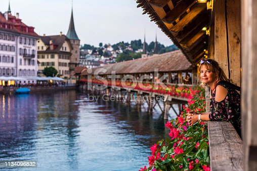 View of the historic Lucerne city from Chapel Bridge with beautiful adult woman at sunset, Switzerland.