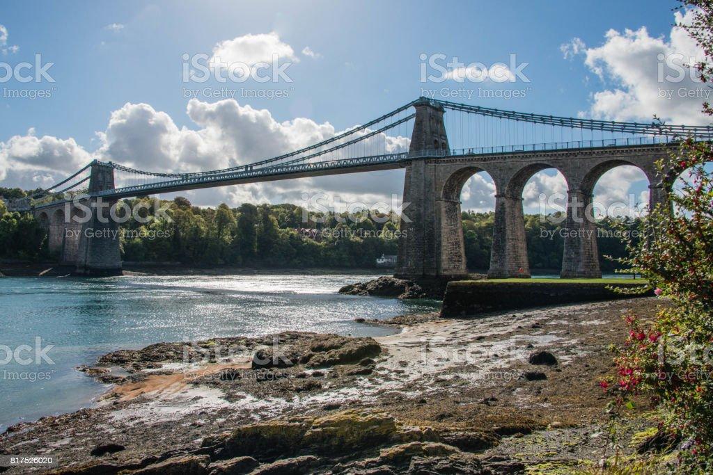 A view of the historic Menai suspension bridge spanning the Menai Straits, Gwynnedd, Wales, UK. stock photo