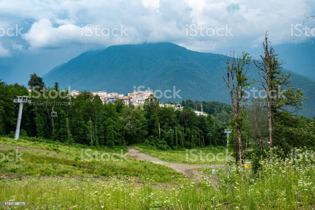 Hotel complex in a green valley surrounded by mountains with cable...