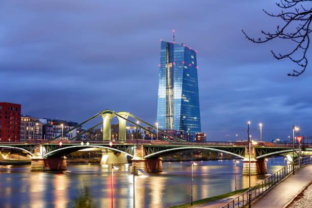 blick auf die beleuchtete skyline frankfurt am main mit flossen brücke und europäische zentralbank in der abenddämmerung - stadt frankfurt stock-fotos und bilder