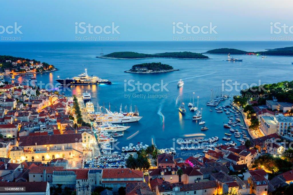 Blick auf die beleuchtete Altstadt Hvar und den Hafen mit Pakleni Inseln in der Abenddämmerung – Foto