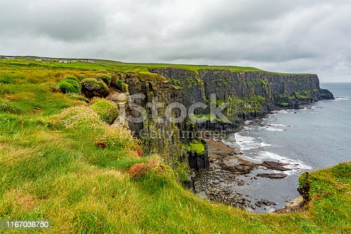 View of the Irish countryside and rocky cliffs along the coastal walk route from Doolin to the Cliffs of Moher, geosites and geopark, Wild Atlantic Way, rainy day in county Clare in Ireland
