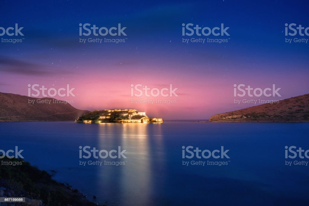 View of the island of Spinalonga at night with nice clouds and calm sea. Here were isolated lepers, humans with the Hansen's desease and took place the story of Victoria 's Hislop novel 'The Island'. stock photo