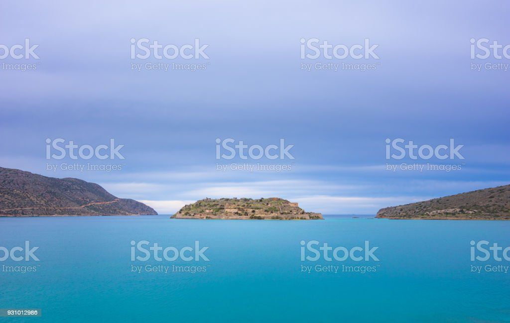 View of the island of Spinalonga with calm sea. Here were isolated lepers, humans with the Hansen's desease, gulf of Elounda, Crete, Greece. stock photo