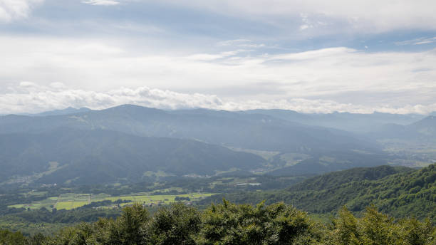 View of the Japanese mountain range and small villages through the sky and the clouds of the Iiyama local area stock photo