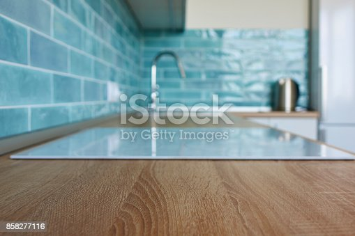 607472174 istock photo View of the kitchen brown countertop with white hob 858277116
