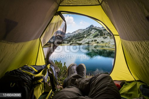 497486952 istock photo View of the lake and mountains through the open window of the tent. 1249340593