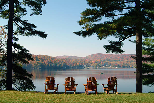 View of the lake in autumn 4 chairs facing the beautiful lake Massawippi in the Eastern Townships, Québec. Photo taken on a calm tranquil colorful morning during the peak autumn foliage season in Ayers Cliff, Quebec. chalet stock pictures, royalty-free photos & images