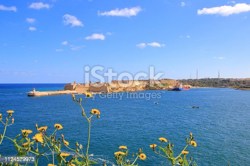The picture was taken on the island of Malta on a sunny day. The photo is a view of the lighthouse and the fort of Ricasoli.
