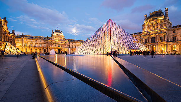 View of the Louvre Museum and the Pyramid at twilight. Paris, France - May 13, 2014: View of the Louvre Museum and the Pyramid at twilight, it is one of the world's largest museums, a historic monument and a central landmark of Paris. musee du louvre stock pictures, royalty-free photos & images