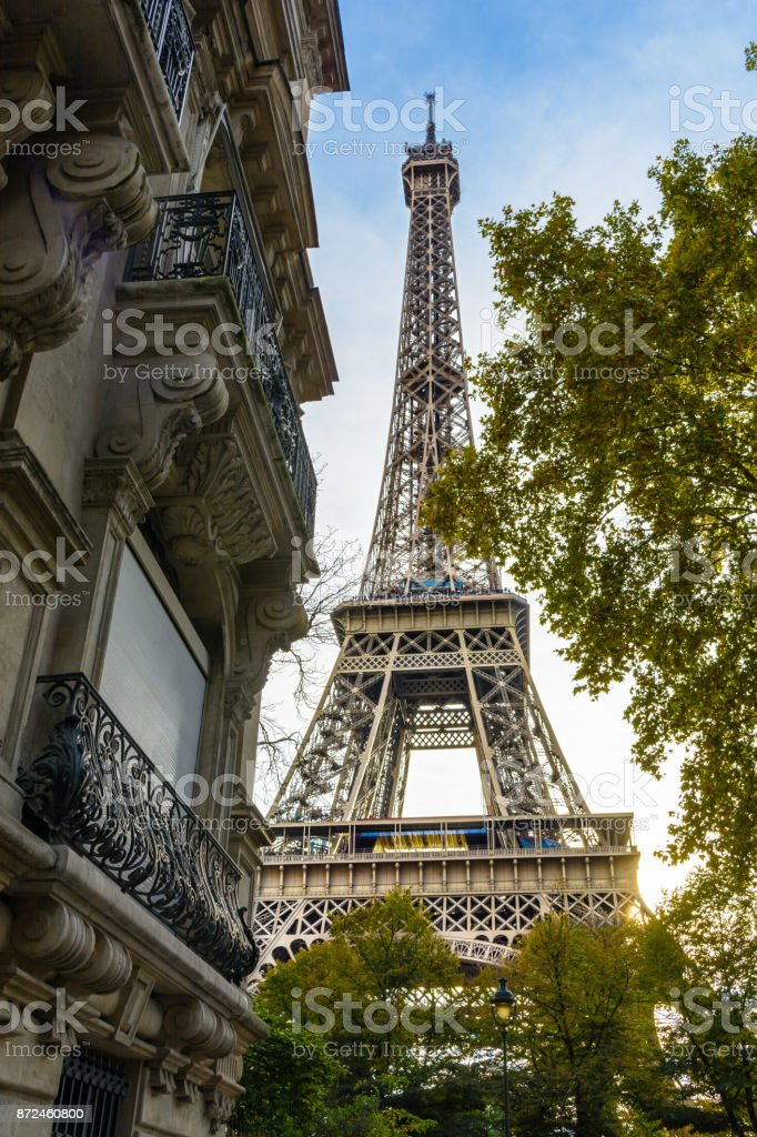 View of the majestic Eiffel Tower in its immediate neighborhood with trees and typical parisian buildings in the foreground stock photo