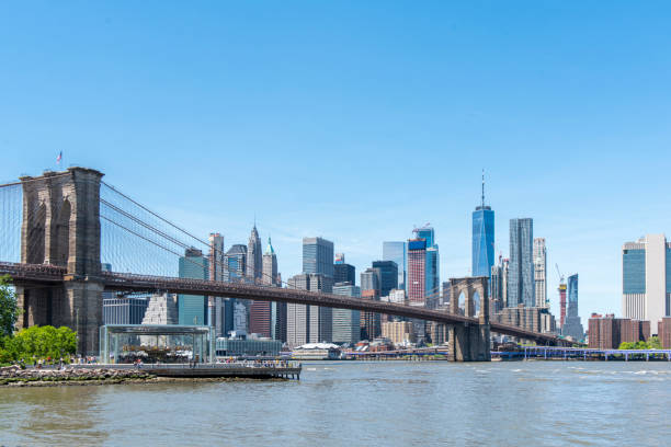 View of the Manhattan Bridge, the coastline and the East River during a sunny springtime day at Brooklyn, New York, USA. stock photo