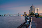 View of the Mississippi river from the city of New Orleans riverfront, with the Great New Orleans Bridge on the background in New Orleans, Louisiana, at dusk.