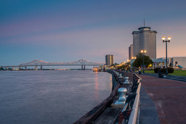 View of the Mississippi river from the city of New Orleans riverfront, with the Great New Orleans Bridge on the background in New Orleans stock photo