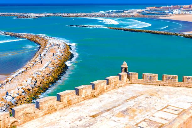 utsikt över havet och vågbrytare som separerar mynningen av floden bou regreg från atlanten. rabat, marocko. - rabat marocko bildbanksfoton och bilder