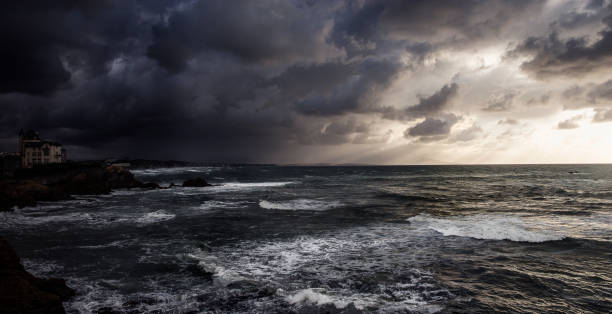 view of the ocean with rocks from biarritz, france, cloudy skie, storm - storm stock photos and pictures
