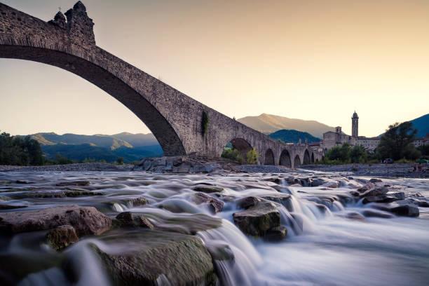 """view of the old medieval bridge, called """"ponte del diavolo"""" or """"ponte gobbo"""" over the river trebbia in the small town of bobbio (northern italy) - bobbio foto e immagini stock"""