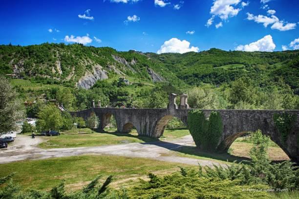 """view of the old medieval bridge, called """"ponte del diavolo"""" or """"ponte gobbo"""" over the river trebbia in the small town of bobbio, piacenza province, italy - bobbio foto e immagini stock"""