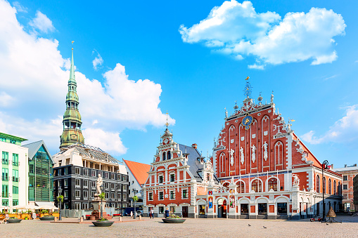 View of the Old Town Ratslaukums square, Roland Statue, The Blackheads House near St Peters Cathedral against blue sky in Riga, Latvia. Summer sunny day