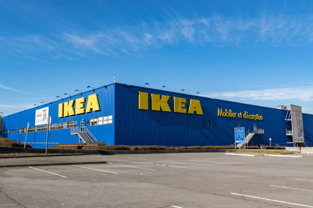 blick auf parkplatz, logo und gebäude des ikea-shops. - ikea tisch stock-fotos und bilder