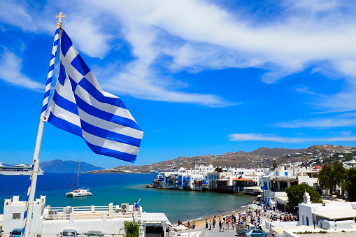 view of the port of Mykonos and the Greek flag from the white windmills in the Cyclades in the heart of the Aegean Sea