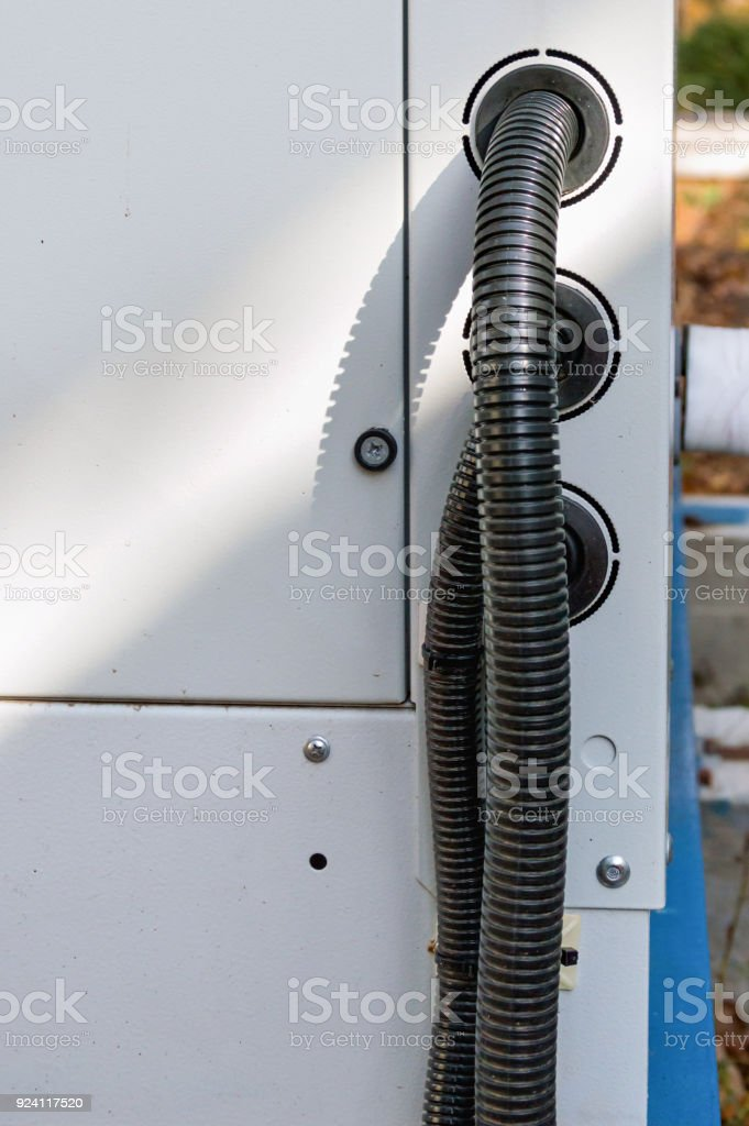 View of the protected wires connected to the industrial cooling unit for central ventilation system stock photo