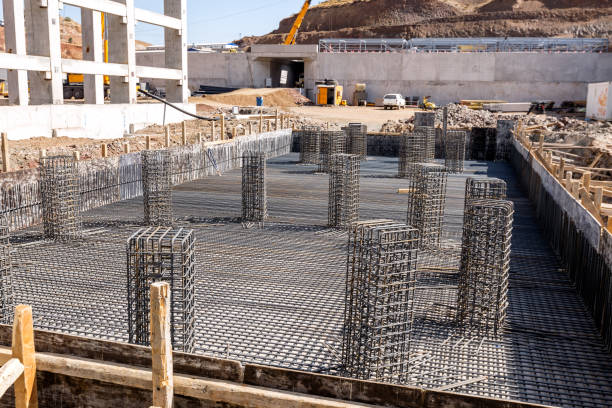 View of the rebar beam cages on the foundation for concrete in the construction site. View of the rebar beam cages on the foundation for concrete in the construction site. rod stock pictures, royalty-free photos & images
