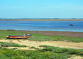 a scenic view of the ribble estuary in lancashire with a small fishing boat on the river and and old derelict speedboat on the shore with grass covered beach sand and bright blue simmer sky