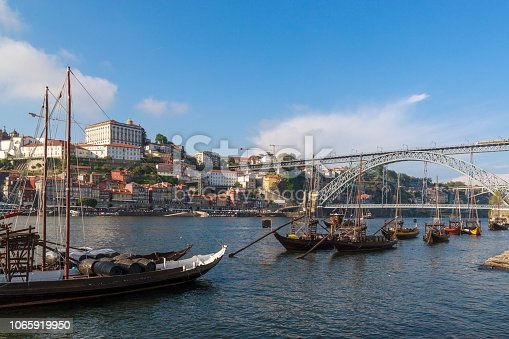 View of the Ribera and bridge Dom Luis I Bridge from Vila Nova de Gaia. The river Douro, Porto, Portugal. Colorful houses on the embankment.  Barrels of port on boats. Travel photography.
