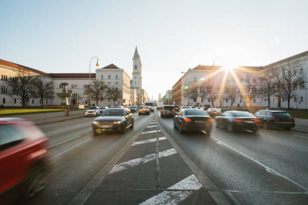 view of the road on the street leopoldstrasse in munich - the capital of bavaria in germany. fast blurred motion car on sunset background. - focus on background stock photos and pictures