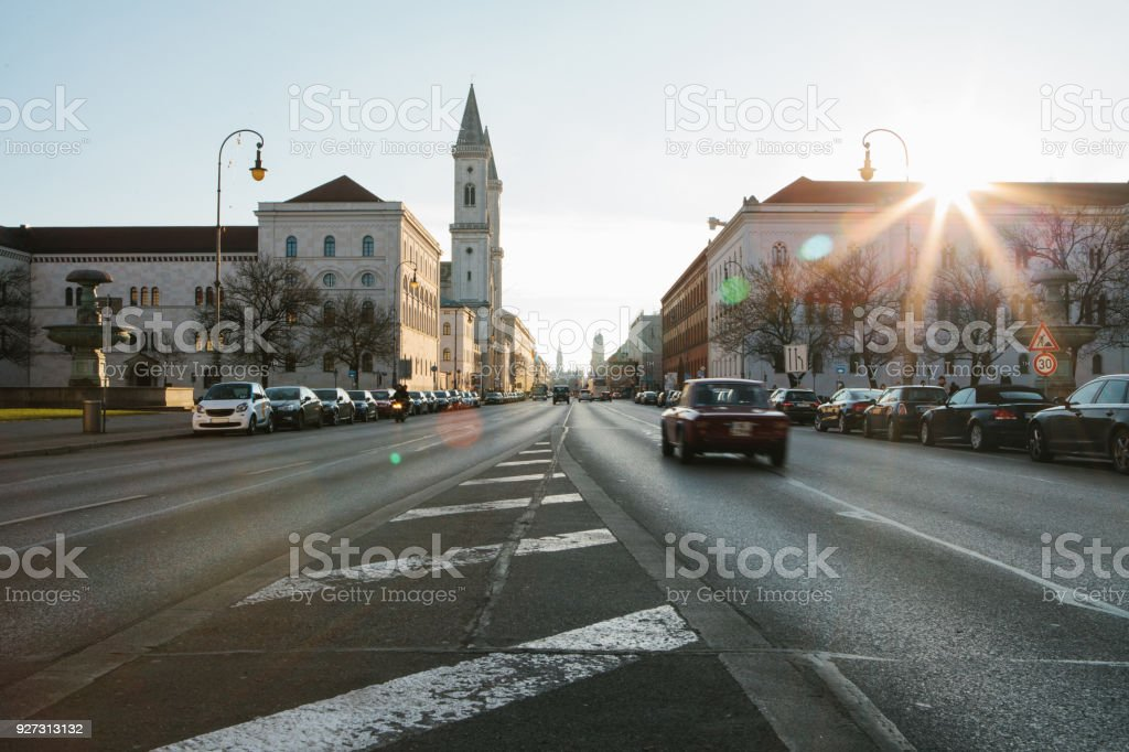 View of the road on the street Leopoldstrasse in Munich - the capital of Bavaria in Germany. Fast blurred motion car on sunset background. stock photo