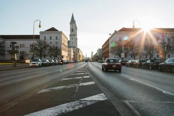 blick von der straße auf die straße leopoldstraße in münchen - die hauptstadt von bayern in deutschland. schnell bewegungsunschärfe auto auf sonnenuntergang hintergrund. - arbeit in münchen stock-fotos und bilder