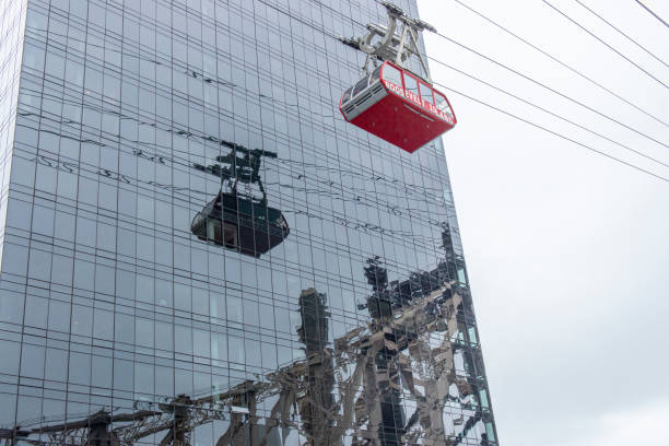 view of the roosevelt island tramway cabin reflected on a building facade at midtown manhattan, new york, usa. - roosevelt island foto e immagini stock