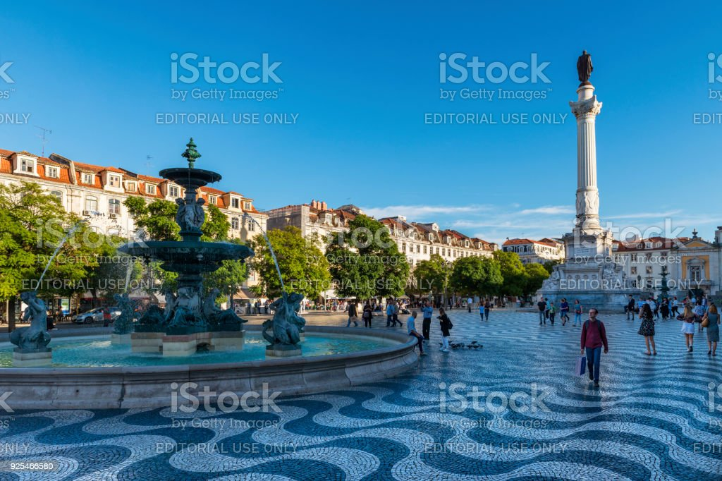 View of the Rossio Square with tourists walking by, in the pombaline downtown of the city of Lisbon stock photo