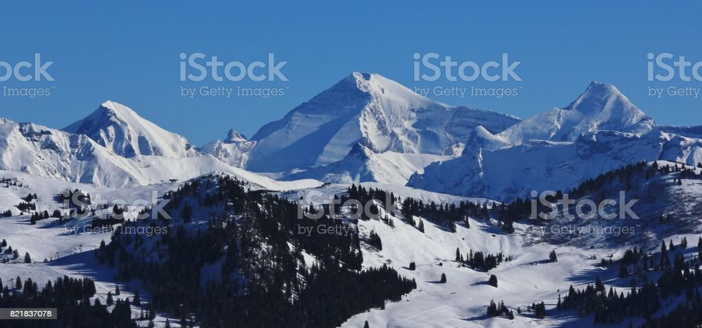 View of the Saanersloch ski slopes and snow covered mountains stock photo
