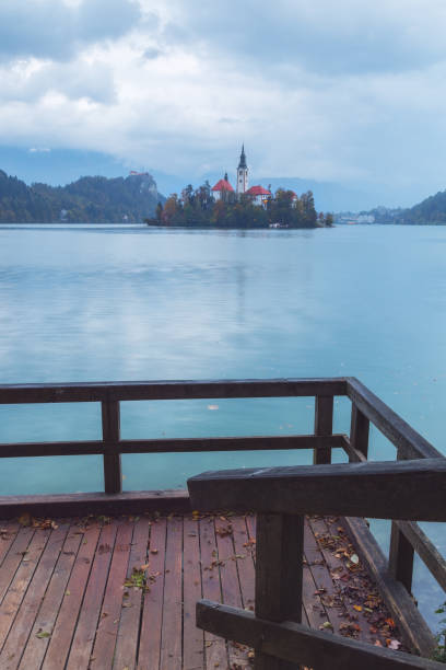 View of the scenic Bled lake from the boardwalk with the Pilgrimage Church of the Assumption of Maria stock photo