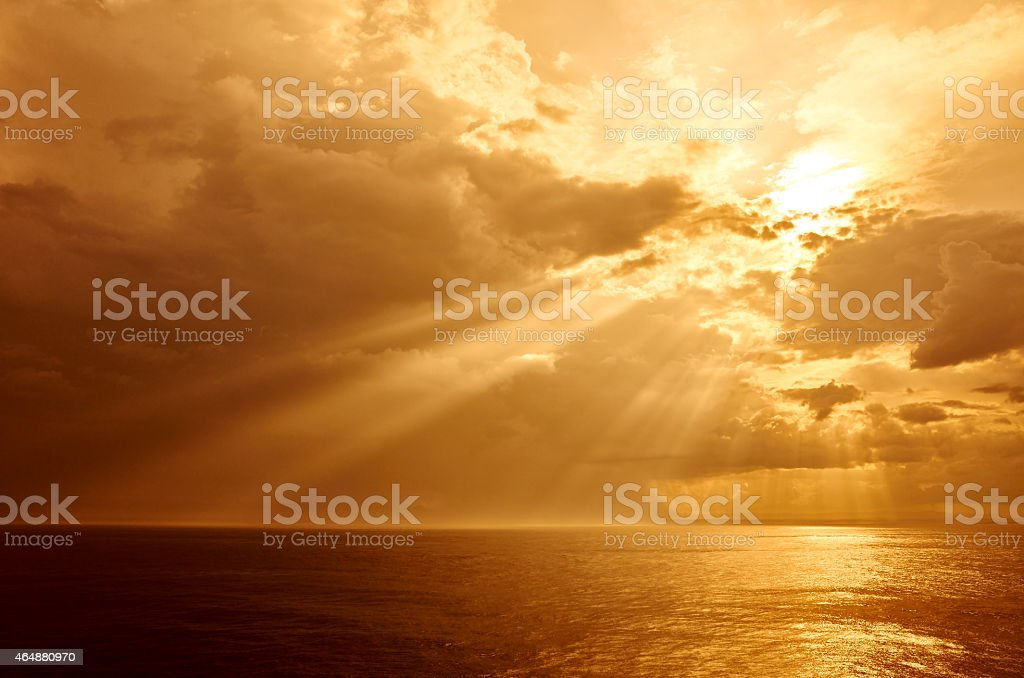 A view of the sea during sunset with a cloudy sky stock photo